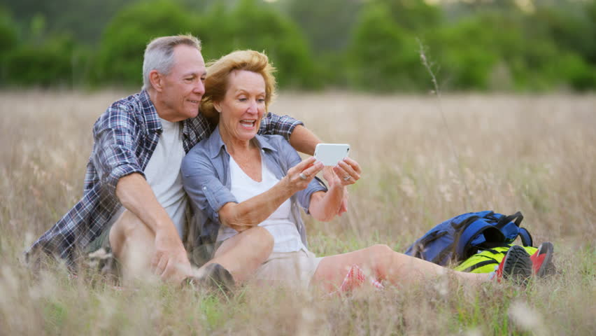 Senior Caucasian American couple using mobile technology for video chat sitting in the countryside outdoors RED DRAGON | Shutterstock HD Video #30307099