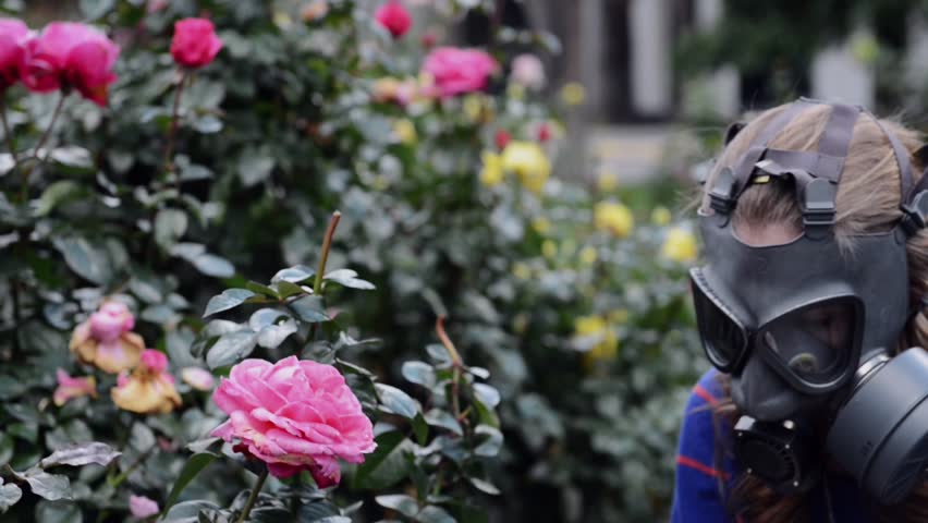 girl in gas mask smells roses