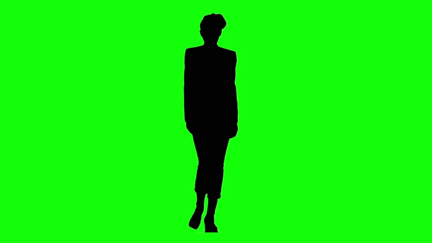 Fashion model girl walking towards the camera in green background, with only a silhouette.