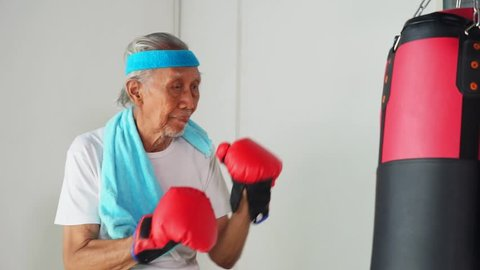 Video footage of healthy Asian elderly punching a boxing sack wearing sportswear and boxing gloves