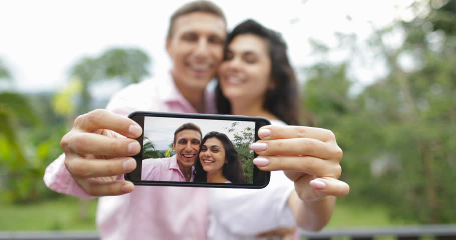Couple Hold Cell Smart Phone Take Selfie Photo Embracing Kissing Outdoors Over Tropical Forest, Young Man And Woman Happy Smiling Lovers Slow Motion 60 | Shutterstock HD Video #30333874