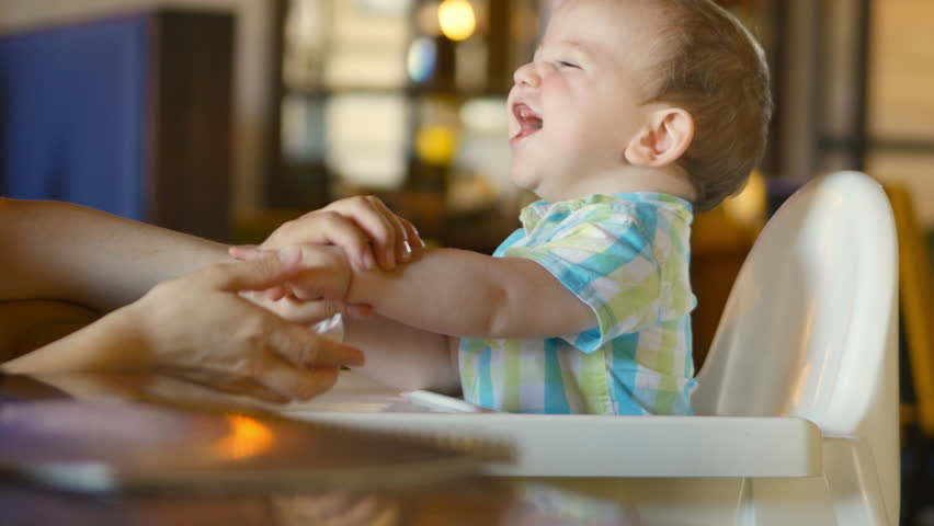 Mom wipes her mouth and hands at the adorable baby. A charming child laughs and claps. 4k.