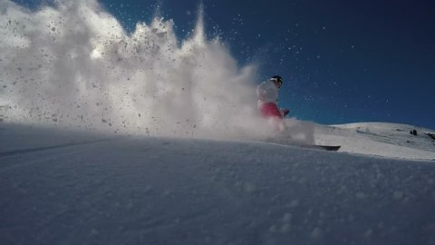 Super slow motion shot of a young woman skiing in the Swiss alps. Skier carving and spraying snow at camera