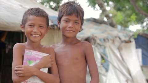 Cambodian boys in slum, shacks at background