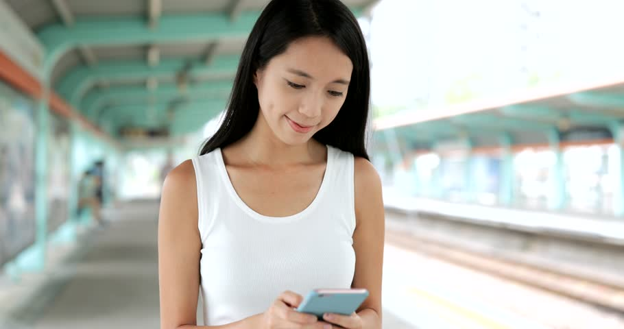 Woman walking in the light rail platform and using cellphone  | Shutterstock HD Video #30375319