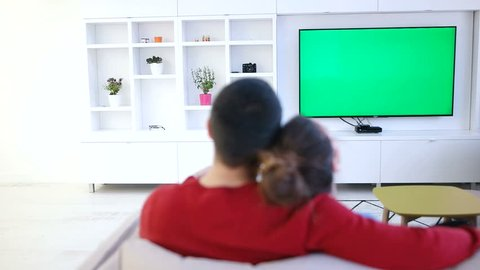 couple relaxing and watching tv in modern apartment