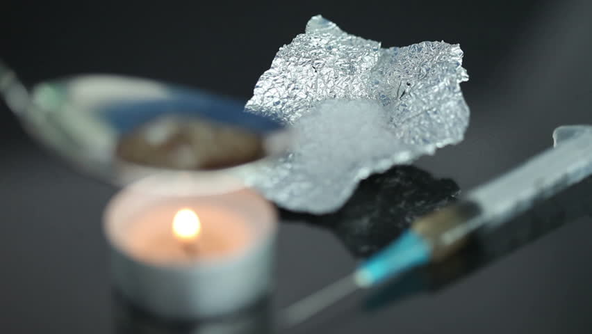 Boiling heroin in a spoon with q syringe being heated by a tea light against a black background