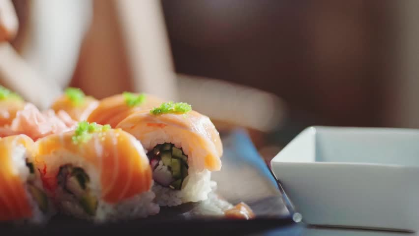 Woman Hand With Chopsticks Dipping Sushi Roll into Soy Sauce. 4K Close Up. Girl eating sushi with salmon on outdoor terrace of Japanese restaurant.