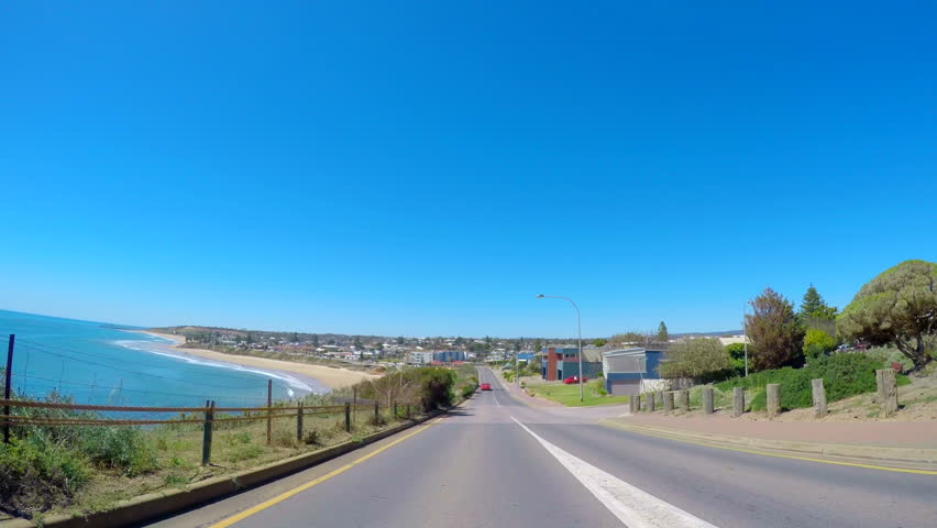 Beautiful coastline driving POV, vehicle driving along The Esplanade, Noarlunga, South Australia, with views of the bay, going over speed humps.