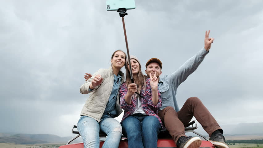 Couple On Road Trip Sit On Convertible Car Taking Selfie 4k