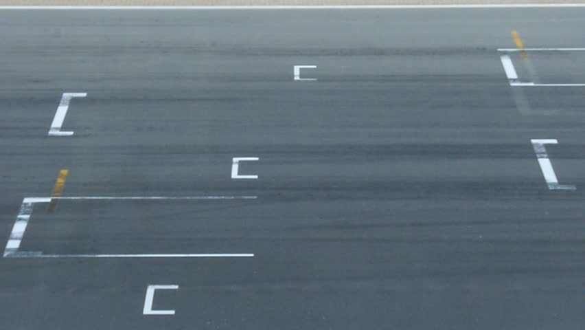 Fast racing cars passing on starting grid.
