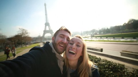 Happy couple in Paris taking selfie-Eiffel tower Happy cheerful couple in Paris in front of the Eiffel tower on the Champs de Mars taking a selfie using a mobile phone.