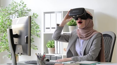 beautiful young lady muslim worker watching 3D video relaxing through virtual reality device.