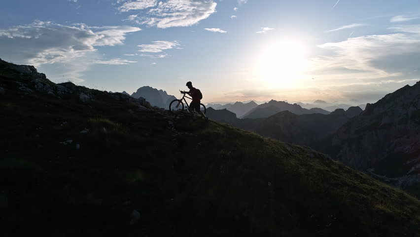 Aerial - Young man pushing his mountain bike up the steep hill at sunset #30441739