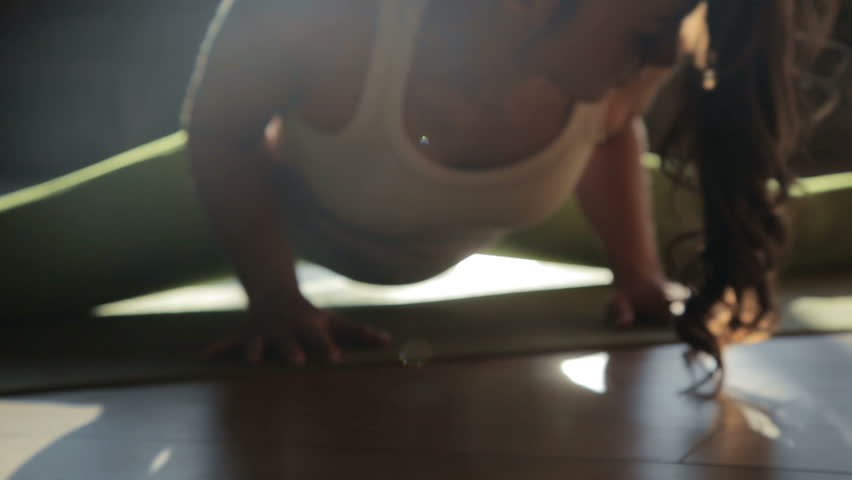 One beautiful 30s sportswoman stretch out legs sitting on matting in fitness-club. Strong active serious athlete concentrated making poses on the wooden floor and control exercising position close up