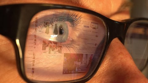 STOCKHOLM - SEPTEMBER 7, 2017: A woman using the social media channel Facebook with an animated screen reflection displayed in her glasses.