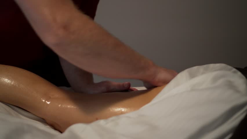 Massage therapist slowly rubbing caucasian woman's leg with large, smooth, black stone. Camera moves right to left with the massage action. Tight | Shutterstock HD Video #30501889