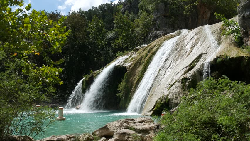 Steady wide angle side view footage of Turner Falls framed by trees leaves and big bushes. The 77-foot Turner Falls is one of the most popular summer destinations in Davis, Oklahoma