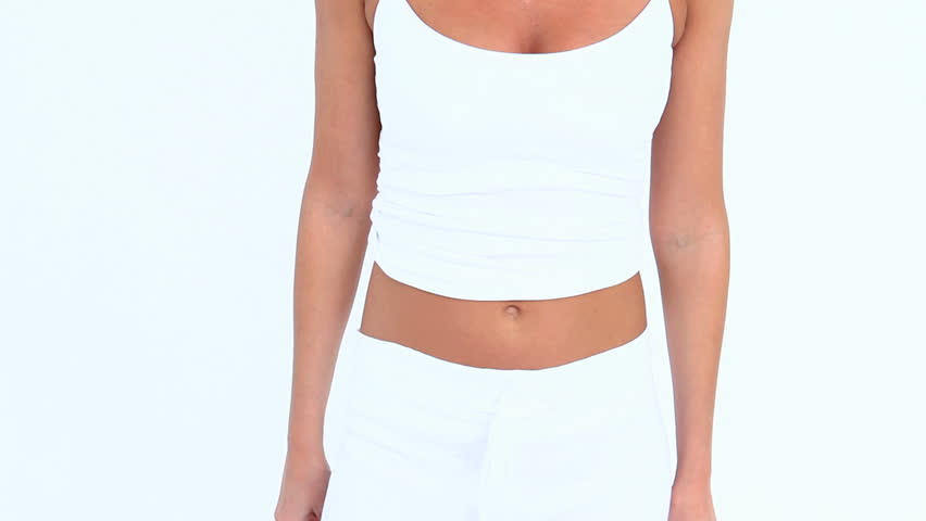 Laughing woman measuring her waist against white background
