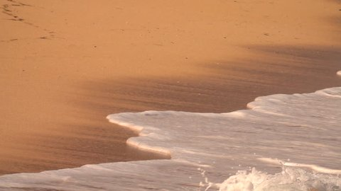 SLOW MOTION, CLOSE UP: Foamy ocean waves washing red sandy beach on tropical paradise island Bali. Swash wave traveling up the gorgeous sea shore with orange sand. Bubbly ripple swashing scenic coast