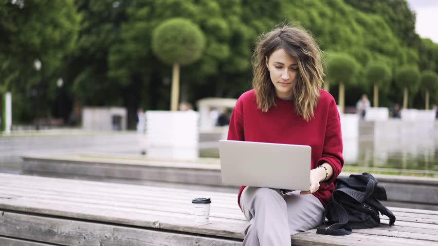 Young girl wearing a red sweatshirt and white pants is sitting near a fountain in a park and working at her laptop. Locked down real time medium shot