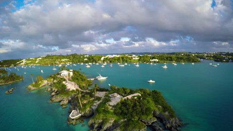 Aerial Views of Bermuda Boats and Sailboats during Sunset with Golden Light and Turquoise Waters and Green Lands with Ominous Clouds in 4K