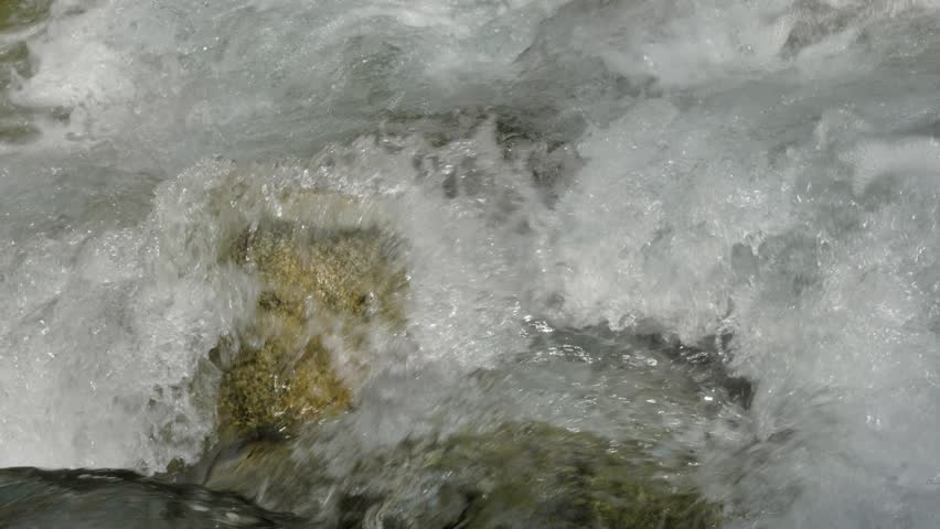 Water in a mountain river in slow motion video. - 4K stock footage clip