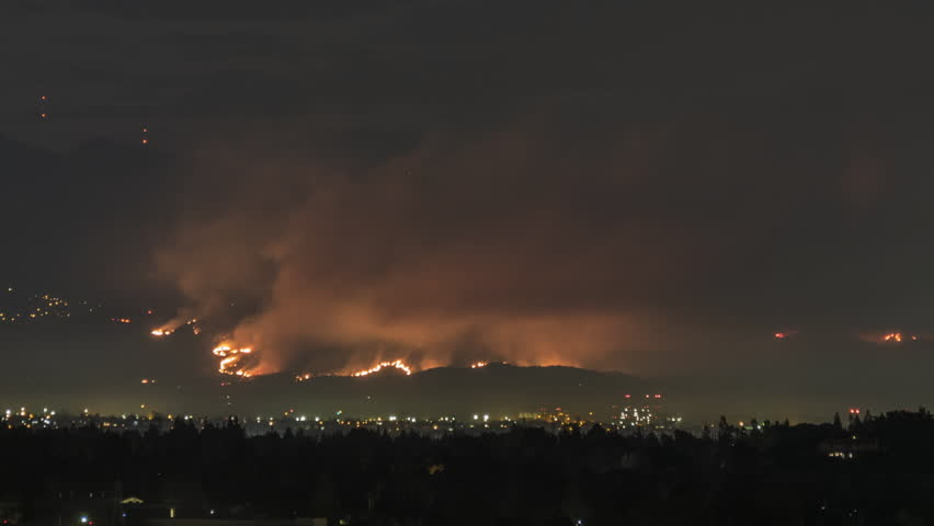 Sunrise time lapse with zoom of La Tuna wildfire burning on Verdugo Mountain near Burbank and Los Angeles, California.
