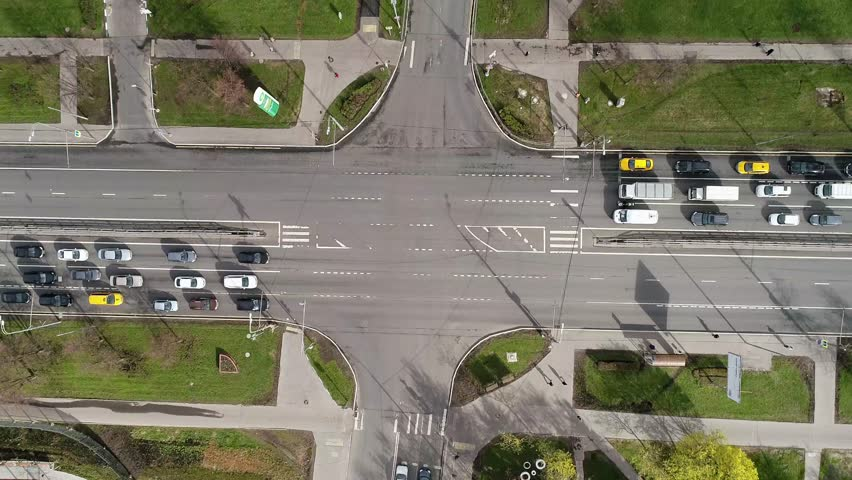 Top view of the road junctions. Aerial survey of highways of the road network. Machines moving at the intersection and denouement. Organization of traffic from a bird's eye view. Summer road.