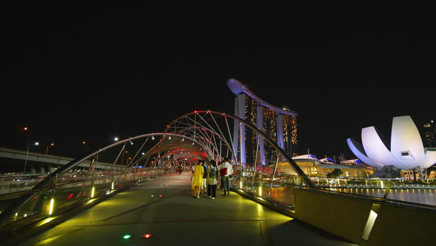 SINGAPORE - 19 AUGUST 2017: 4k Video of walking tourist the Helix Bridge in central Singapore Harbor at Night on 19 AUGUST 2017 in Singapore. | Shutterstock HD Video #30550909