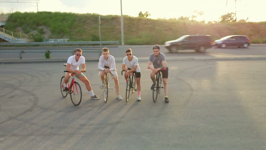 Four young beautiful bicyclist staying with bikes empty road dawn drone footage  | Shutterstock HD Video #30563059