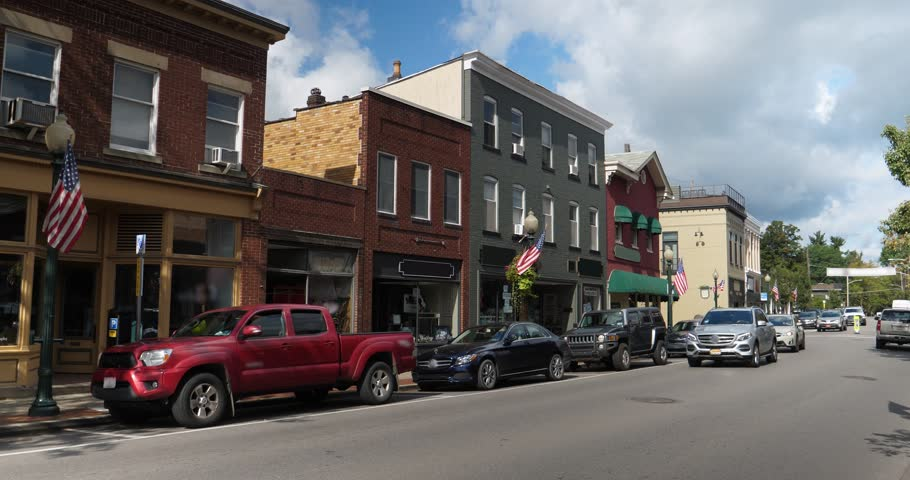 A daytime exterior establishing shot of a generic small town's Main Street shopping district storefronts and traffic. Store marquees digitally removed for customization.