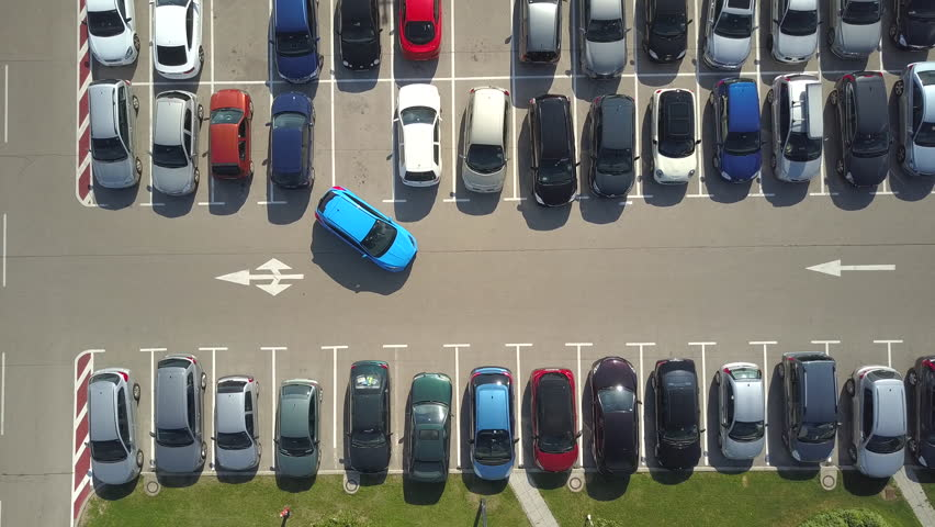AERIAL TOP DOWN: Flying above bad driver incapable to park a car on parking space in crowded parking lot. Driver having problems, unable to park a car in parking spot. Parking fail on parkspace