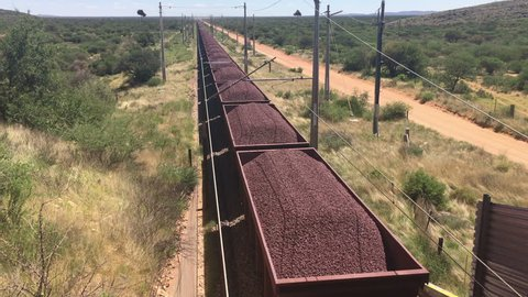 Iron ore being transported on railroad trucks by a very long freight train, South Africa