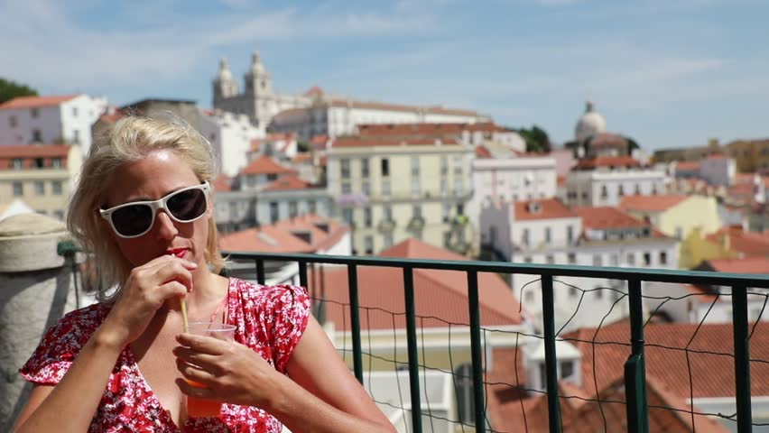 Happy tourist woman drinking orange juice admiring Alfama from Miradouro das Portas do Sol. Overlook of Lisbon in Portugal, Europe. Lisbon aerial view of Church of Sao Vicente of Fora. Slow motion.