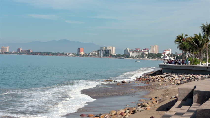 PUERTO VALLARTA, MEXICO NOV 2012: Tourism income. Boardwalk Malecon beach and tourist area shore Banderas Bay, Pacific Ocean. Friends and family stroll and walk along sea shore, restaurants and cafes.
