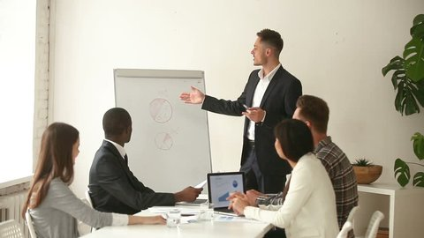 Confident white businessman gives presentation to diverse colleagues at briefing in meeting room, business coach shows charts on whiteboard, team leader explains employees project marketing strategy