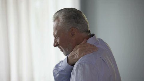 Aged man standing sideways, touching neck in acute pain, trying to move head