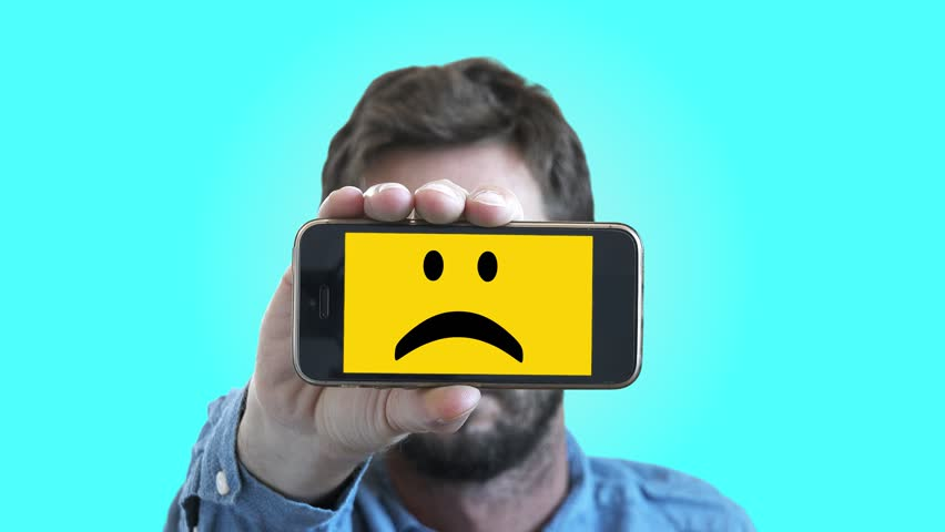 Sad Smiley Face Man On Smartphone Screen. Man shows his feelings through a smartphone with a sad Smiley face on screen