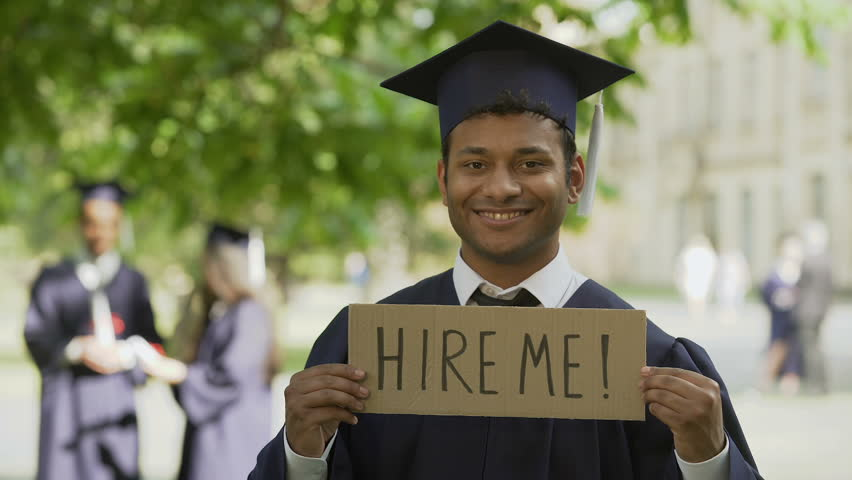Student in graduation clothes putting up table hire me job opportunity for youth