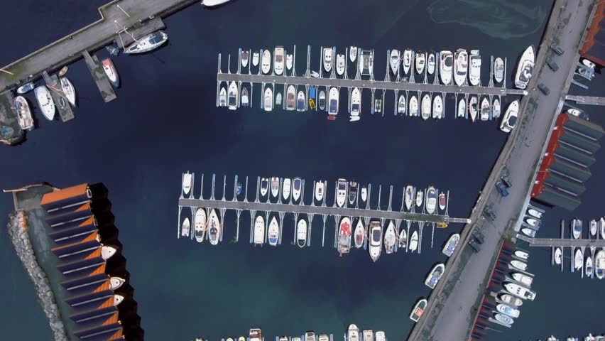 Camera rotation. Ships standing near the pier in evening. Parking for water transport, boathouse, seafront. Amazing top view of harbor with wonderful white boats and yachts. Norway.