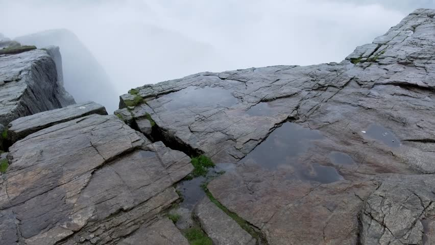 Someone, something approach the edge of abyss at high altitude, break off. Preikestolen Landscape, Prekestolen, Preacher's Pulpit, Pulpit Rock. Magnificent scenery, mountains, steep cliffs in the fog #30628489