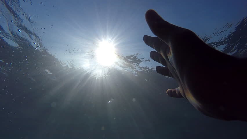 Point of view of man drowning in the sea or ocean. Arm asking for help and trying to reach to the sun. Male hand stretches from under the water to sunrays. Slow motion POV