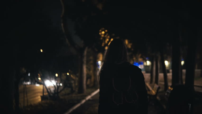 Back view of tourist woman with backpack walking through the dark park near the road late at night alone.