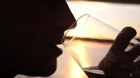 A man enjoys evening and sunset, drinks wine from a glass goblet. HD, 1920x1080. slow motion