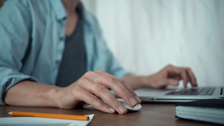 Male hands using wireless mouse making note with pencil at printed analyzing graphs. Young man using laptop at office | Shutterstock HD Video #30681229