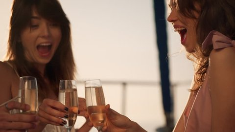 slow motion happy friends clinking glasses with sparkling wine enjoying carefree time laughing in summer time while yachting closeup