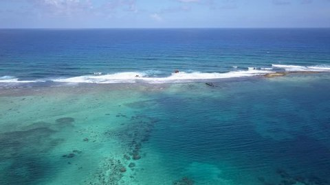 Aerial fly of flying backwards from an old shipwreck located on a large, fringing, tropical coral reef
