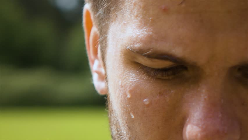 Epic extreme close-up shot of sweaty man outdoor in park. Drop of water on his face macro slow motion. Turning head from dowm to camera