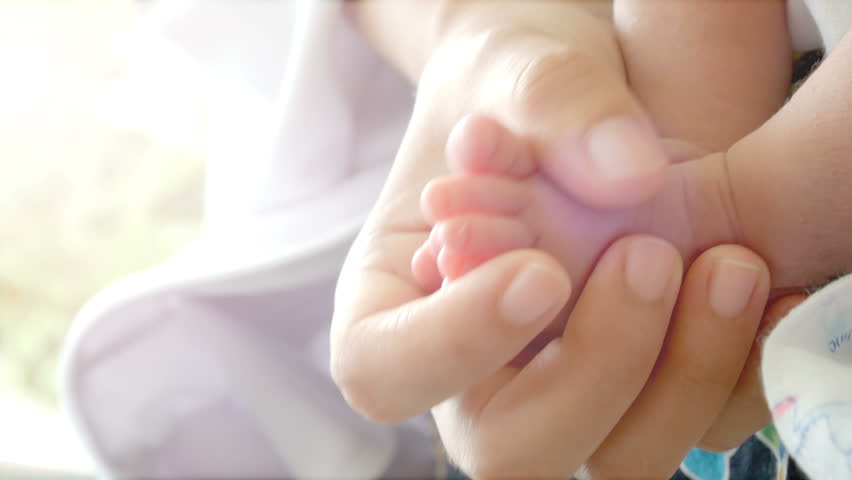 Close-up of parents hands holding feet newborn and baby sleep on her arms. Concept of happy family desire in no noisy home and carefree. #30728629